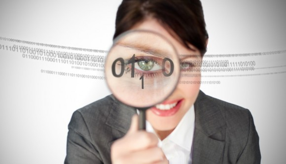 Woman looking through magnifying glass while smiling at numbers